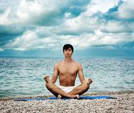 Homem que faz a ioga perto do mar imagens de stock royalty free