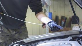 Homem que faz a manutenção que verifica o nível de óleo após a mudança de óleo no motor de automóveis dentro no fundo amarelo video estoque