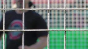 Homem que faz o esporte atrás da cerca