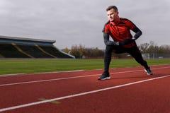 Homem que faz o esticão na pista de atletismo exterior Imagem de Stock Royalty Free