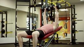 Homem que faz o exercício da imprensa de banco do peso no gym filme