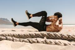 Homem que faz o exercício do abdômen na praia fotos de stock