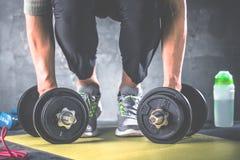 Homem que faz o exercício no gym em esteiras da ioga imagens de stock royalty free
