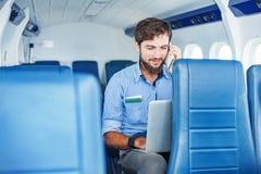 Homem que faz o negócio no avião imagem de stock royalty free