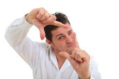 Homem que faz o quadro com seus dedos Fotografia de Stock