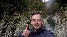 Homem que faz o selfie e que mostra o polegar acima na porta do diabo da garganta em Sochi, Rússia video estoque