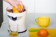 Homem que faz o suco de laranja fresco na cozinha Fotos de Stock Royalty Free