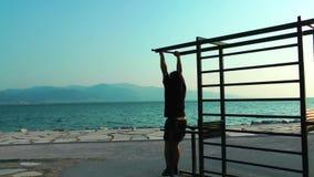 Homem que faz o treinamento do esporte perto do beira-mar para o ajuste e a vida saudável filme
