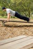 Homem que faz a parte externa dos Push-ups - vertical Fotografia de Stock Royalty Free