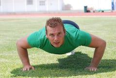 Homem que faz push-ups Imagens de Stock