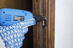 Homem que faz reparos em casa Buraco da fechadura de fixação na sala usando a chave de fenda elétrica fotos de stock