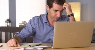 Homem que faz seus impostos na mesa Fotografia de Stock Royalty Free