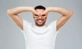 Homem que faz vidros de dedo sobre o fundo cinzento Imagem de Stock Royalty Free