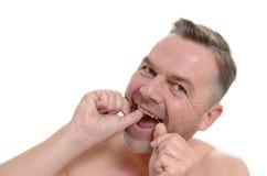 Homem que flossing seus dentes com fio dental Imagens de Stock Royalty Free