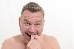 Homem que flossing seus dentes com fio dental Fotografia de Stock Royalty Free