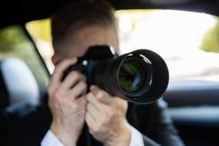 Homem que fotografa com câmera de SLR imagens de stock royalty free