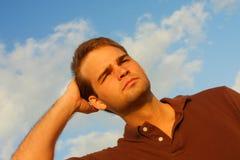 Homem que fricciona seu cabelo fotografia de stock