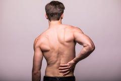 Homem que fricciona sua parte traseira dolorosa no cinza Alívio das dores, conceito da quiroterapia imagem de stock