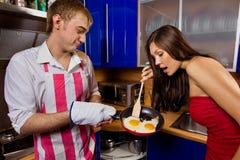 Homem que frita ovos para sua amiga Fotografia de Stock