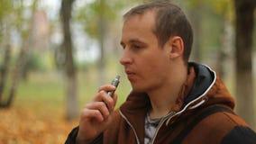 Homem que fuma o sigarette eletrônico exterior video estoque