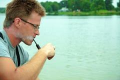 Homem que fuma uma tubulação Fotografia de Stock Royalty Free