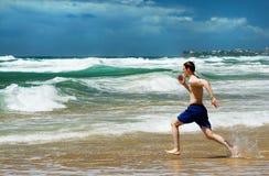 Homem que funciona na praia Fotografia de Stock Royalty Free