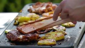 Homem que grelha salsichas, peitos de frango, cebola e anéis do potatoe exteriores no jardim filme