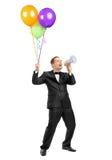 Homem que grita o throw um megafone e que prende balões Foto de Stock Royalty Free