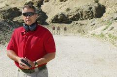 Homem que guarda a arma da mão na escala de acendimento Fotos de Stock