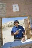 Homem que guarda a arma da mão na escala de acendimento Foto de Stock Royalty Free