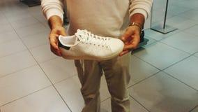 Homem que guarda as sapatilhas Fotos de Stock Royalty Free