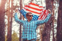 Homem que guarda a bandeira dos EUA Comemorando o Dia da Independência de América 4 de julho Homem que tem o divertimento América Foto de Stock Royalty Free