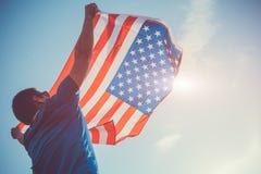 Homem que guarda a bandeira nacional dos EUA Comemorando o Dia da Independência de América 4 de julho Foto de Stock Royalty Free