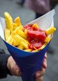 Homem que guarda batatas fritas no cartucho de papel com ketchup Alimento da rua fotos de stock royalty free