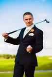 Homem que guarda a bola e a madeira do golfe Fotografia de Stock