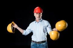 Homem que guarda capacetes de segurança Foto de Stock Royalty Free