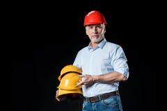 Homem que guarda capacetes de segurança Fotos de Stock