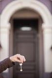 Homem que guarda chaves na frente da porta da casa Fotografia de Stock Royalty Free