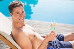 Homem que guarda a flauta de champanhe pela piscina Foto de Stock Royalty Free