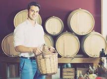 Homem que guarda a garrafa de vime grande com vinho Fotografia de Stock Royalty Free