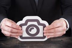 Homem que guarda o ícone da câmera nas mãos Fotos de Stock Royalty Free