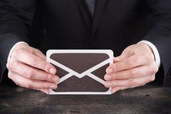Homem que guarda o ícone do email nas mãos Imagem de Stock