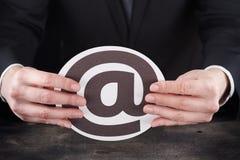 Homem que guarda o ícone do email nas mãos Foto de Stock Royalty Free