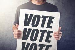 Homem que guarda o cartaz com etiqueta do voto fotografia de stock royalty free
