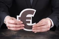 Homem que guarda o euro- ícone nas mãos Imagens de Stock