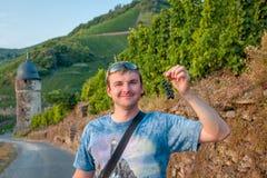 Homem que guarda o grupo de uvas Imagem de Stock
