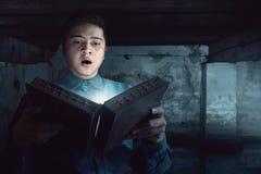 Homem que guarda o livro mágico Fotografia de Stock