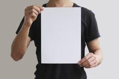 Homem que guarda o papel A4 branco verticalmente Fotos de Stock