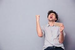 Homem que guarda o smartphone e que comemora seu sucesso Fotografia de Stock Royalty Free