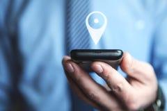 Homem que guarda o telefone com ícone de GPS Conceito da navegação móvel Imagem de Stock Royalty Free